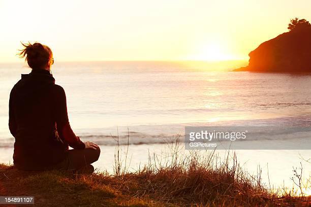 Mulher meditar no Penhasco no oceano