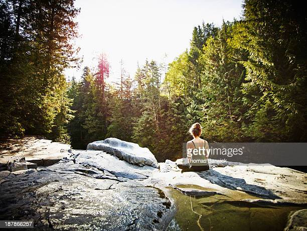 Woman meditating on rock in forest