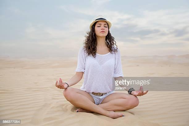Woman meditating on sand sune