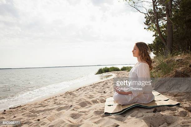 Woman meditating on sea shore at beach against sky