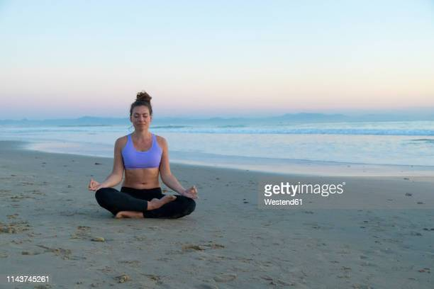 woman meditating on the beach in the evening - yogi stock pictures, royalty-free photos & images