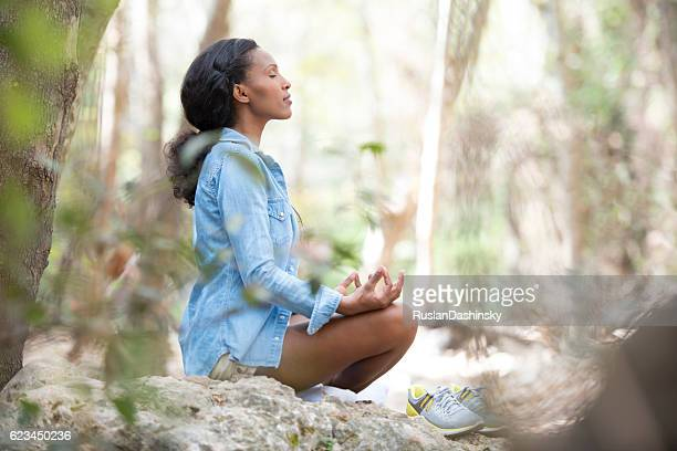 Woman meditating outdoors.