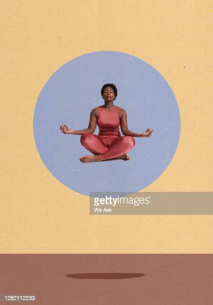 woman meditating sitting crosslegged - young women stock pictures, royalty-free photos & images