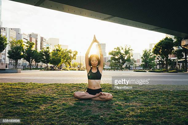Woman Meditating Under The Bridge At Sunset