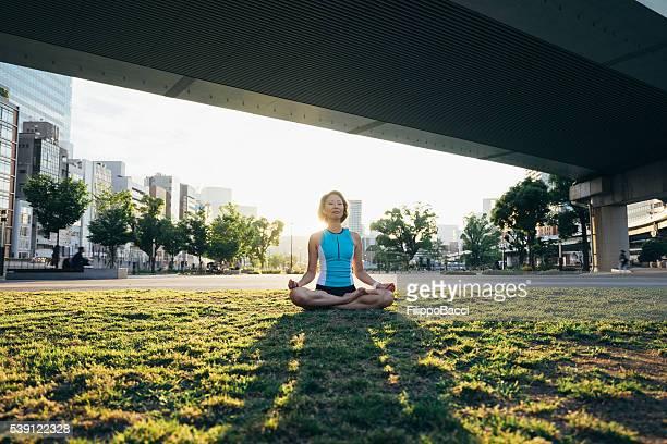 女性瞑想する橋の下で日没に