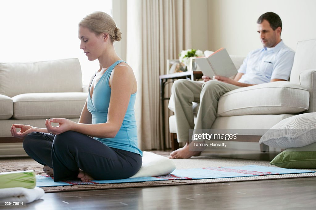 Woman meditating while husband reads : Stock-Foto