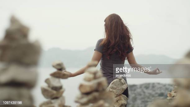 woman meditation. rocky coastline - hot spanish women stock pictures, royalty-free photos & images