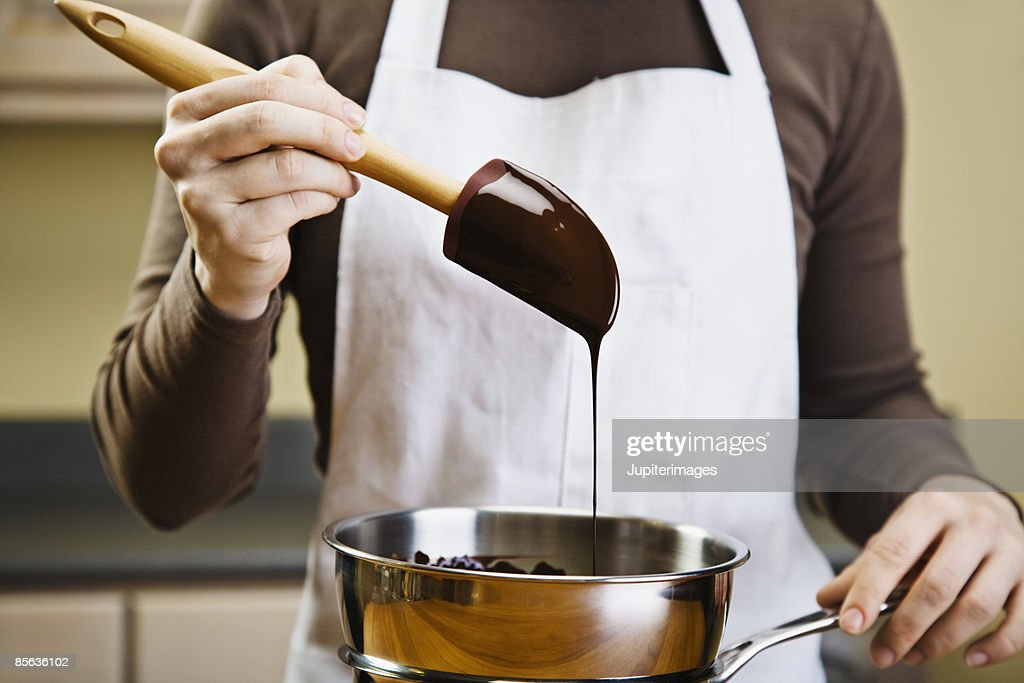 Woman melting chocolate in double boiler : Stock Photo