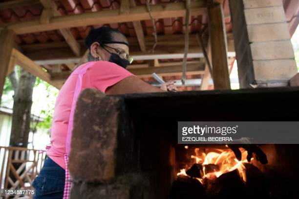 Woman, member of a company of typical food, arranges fire to cook for tourists in Guanacaste, Costa Rica, on August 24, 2021. - Costa Rica has...