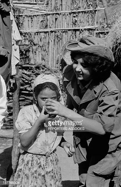 A woman member of ALN National Liberation Army gives a glass of water to a little girl on September 13 1962 in Algeria