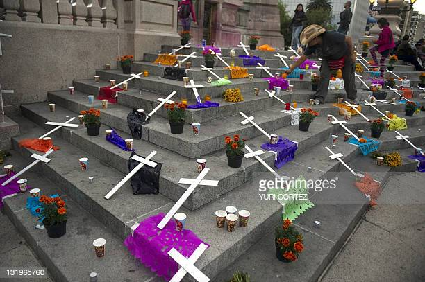 A woman member of Movement for Peace with Justice and Dignity leaded by Mexican poet Javier Sicilia places flowers in an altar in memory of more than...