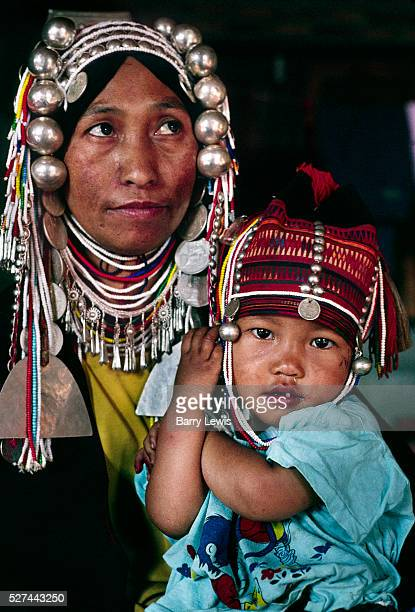 Woman member of the Akha Tribe with her child wearing an ornate silver headdress and necklaces The village lies near the Burmese border and the tribe...