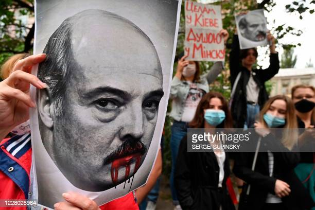 TOPSHOT A woman member of the Belarus diaspora holds a placard depicting Alexander Lukashenko with blood on his mouth and moustache as she with...