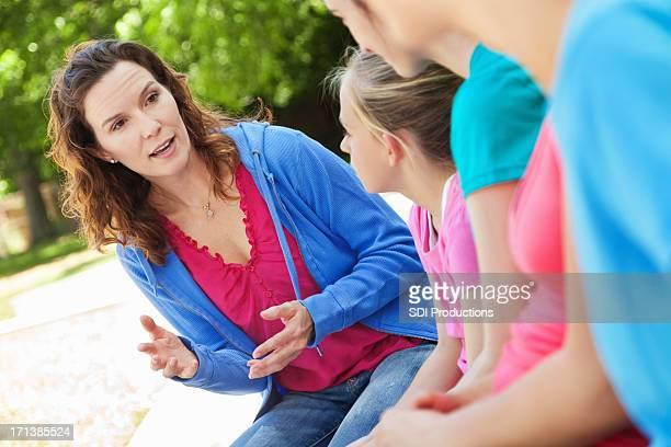 Frau mentoring Gruppe von preteen Mädchen im Freien park