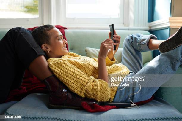 woman messaging on phone while leaning on friend - sofa stock-fotos und bilder