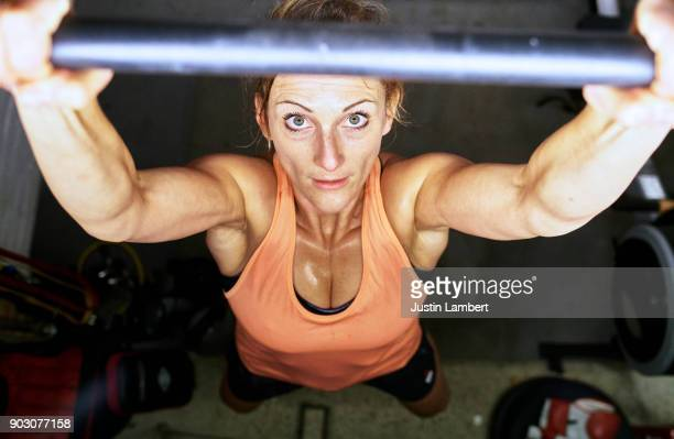 Woman mid exercise performing pull up in home gym