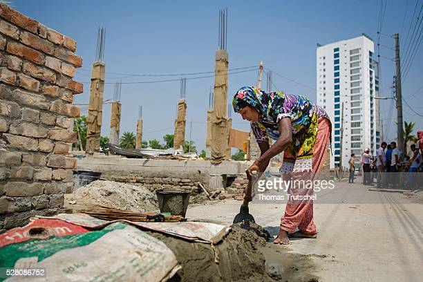 A woman mixes cement in front of a newly built building on April 11 2016 in Khulna Bangladesh