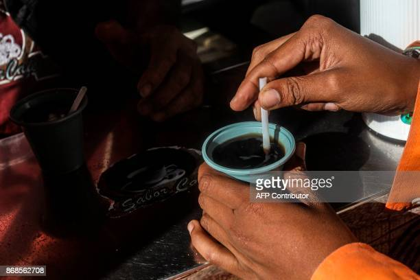 A woman mixes sugar in a coffee at the Berrio square in Medellin on October 30 2017 October is the peak of the high season coffee harvest in the...