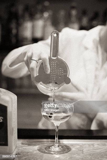 A woman mixing a cocktail, a mixologist at work.