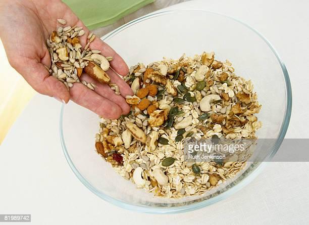 Woman mixing nuts into muesli, close up