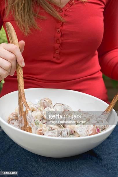 Woman mixing potato salad with salad servers