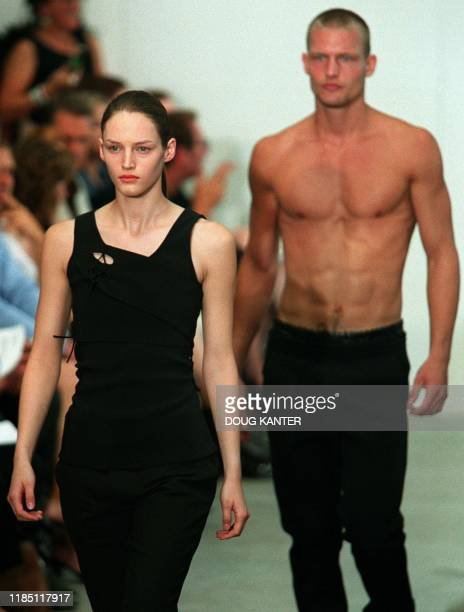 A woman model in a black top and pants and a male model in black pants make their way down the runway during the Helmut Lang show during Spring 2001...