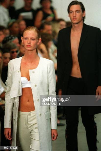 A woman model in white pants jacket and top and a male model in a black jacket and pants make their way down the runway during the Helmut Lang show...