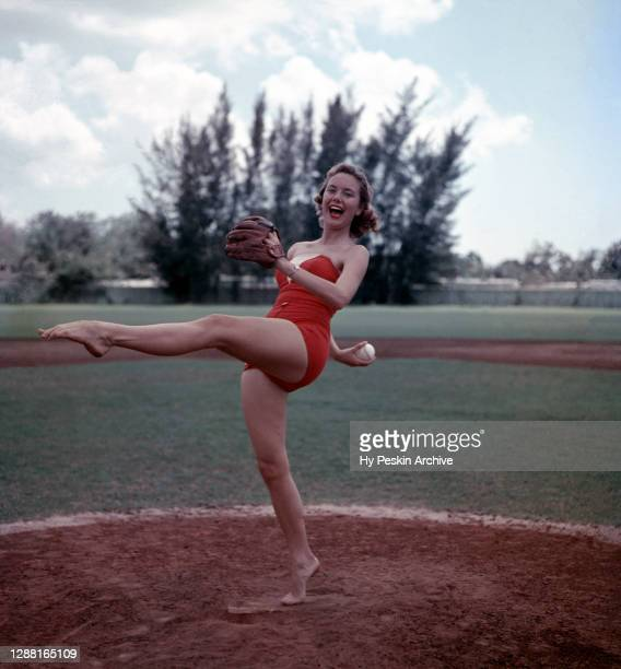 Woman model is ready to throw the pitch as she stands on the pitching mound circa 1950's.
