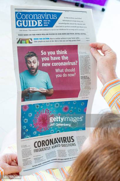 Woman model released holding newspaper with Coronavirus Frequently asked Questions