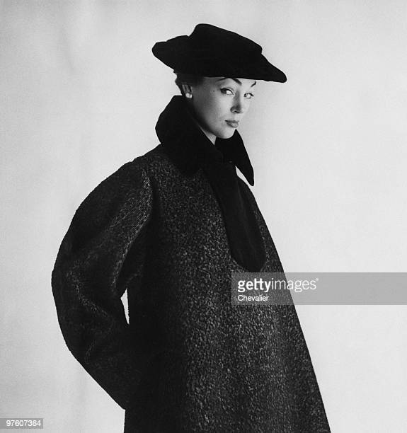 A woman modelling a grey wool coat with black velvet trim and matching hat by Castillo at Lanvin October 1951 Original publication Picture Post 5539...