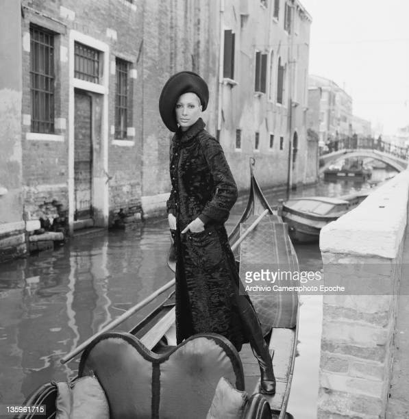 A woman modelling a Pierre Cardin outfit of threequarter length vented coat with kneelength boots and asymmetrical hat Venice circa 1965