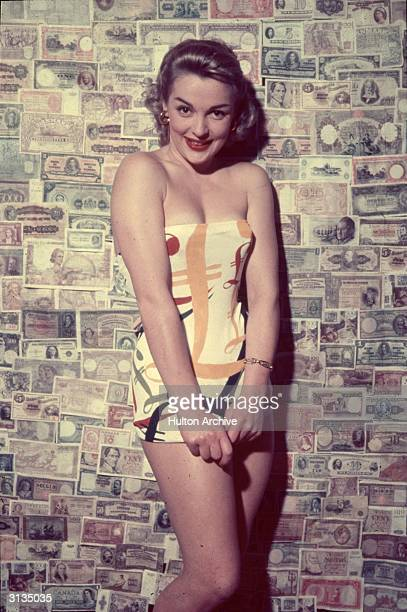 A woman modelling a pound print swimming costume against a backdrop of banknotes