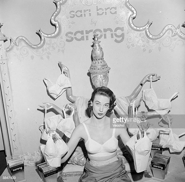 A woman modelling a 'Sarong' brand sari bra whilst holding one on in each of her outstretched hands She is standing in front of an effigy of an...