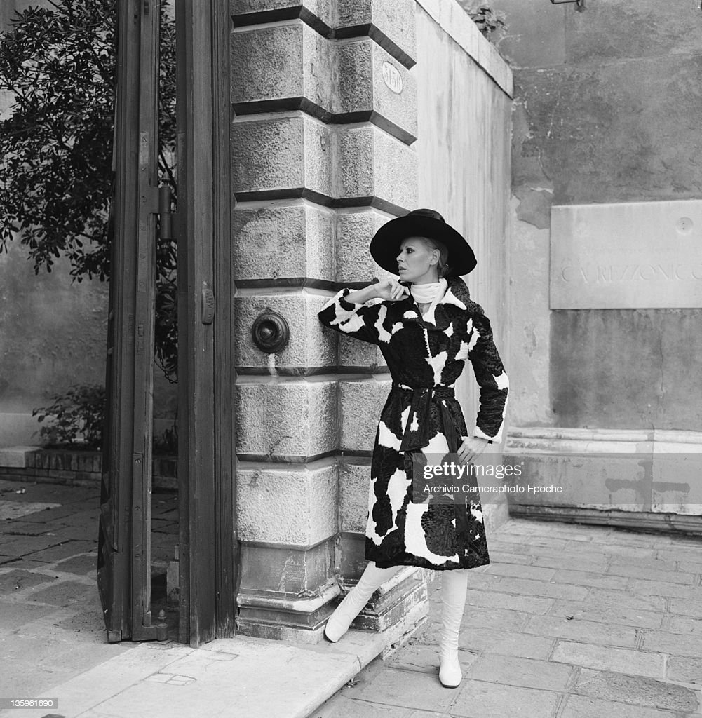 A woman modelling a Schiaparelli outfit of cow-hide coat with wide-brimmed hat and white boots, circa 1965.