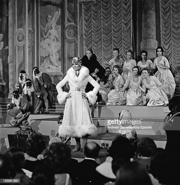 Woman modelling a three-quarter length coat with fur trim at a fashion show, circa 1957. In the background are men in Venetian carnival costumes and...