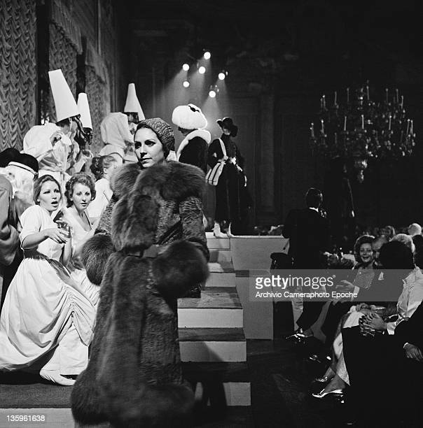 Woman modelling a three-quarter length fur coat at a fashion show, circa 1957. In the background are men in Venetian carnival costumes and beaked...