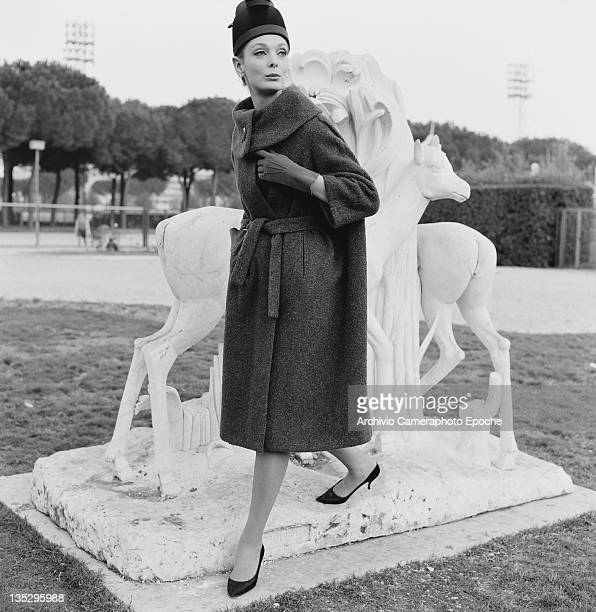 Woman modelling a three-quarter length winter coat and matching brimless hat, Rome, circa 1957.