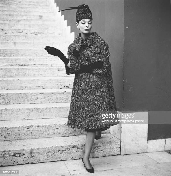 A woman modelling a threequarter length winter coat and matching brimless hat with feather trim Rome circa 1957