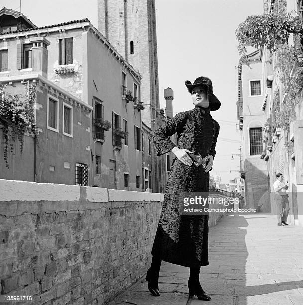 Woman modelling an Yves Saint Laurent outfit of three-quarter length coat and soft hat, Venice, circa 1965.
