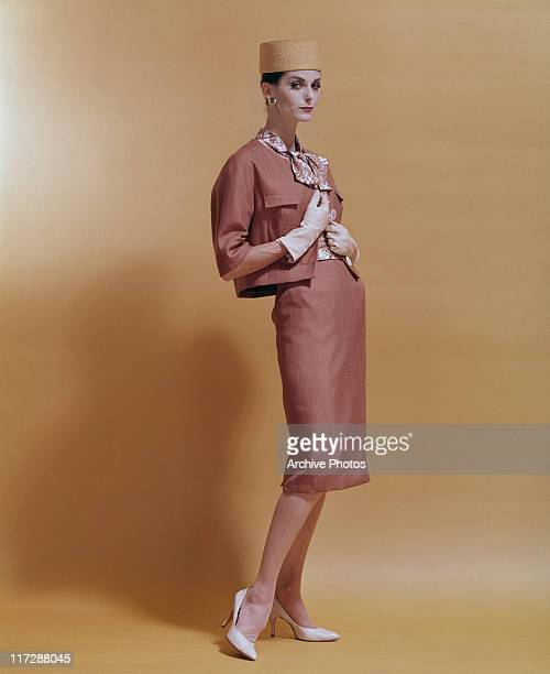 A woman modelling women's fashions in a studio portrait standing wearing a salmon pink twopiece outfit with a patterned blouse white gloves white...