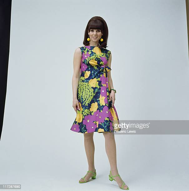 A woman modelling women's fashions in a studio portrait wearing a dark blue lilac green and yellow floral print dress with yellow drop earrings and...