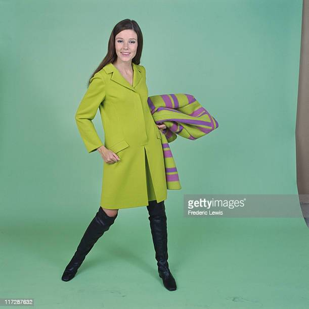 A woman modelling women's fashions in a studio portrait wearing a light green coat with black kneehigh boots and holding a green and purple overcoat...