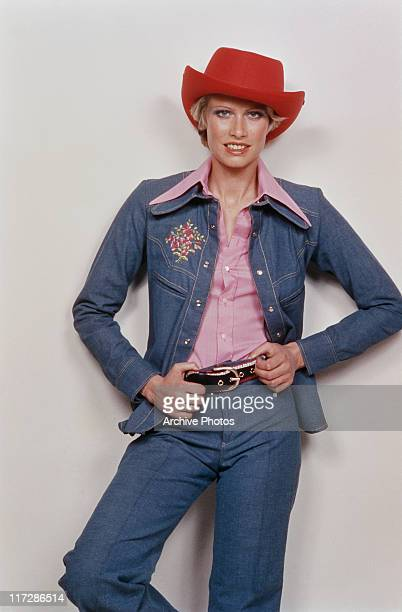 A woman modelling women's fashions in a studio portrait wearing a red cowboy hat and a blue denim trouser suit with a pink blouse with the collar...
