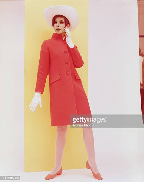 Woman modelling women's fashions in a studio portrait, wearing a red coat, with white wide-brimmed hat, white gloves and red shoes, 1966.