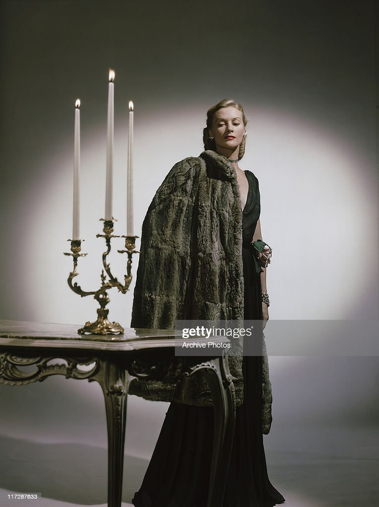 A woman modelling women's fashions in a studio portrait, wearing black gown, with a grey fur coat over her shoulder as she poses beside a table on which sits a candelabra with three lit candles, circa 1948.