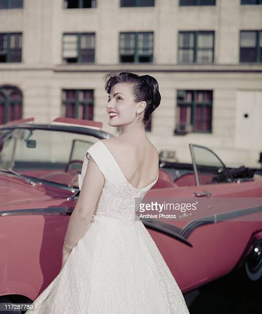 A woman modelling women's fashions smiling as she looks over her shoulder wearing a white dress and posing beside a pink vintage motor car circa 1960