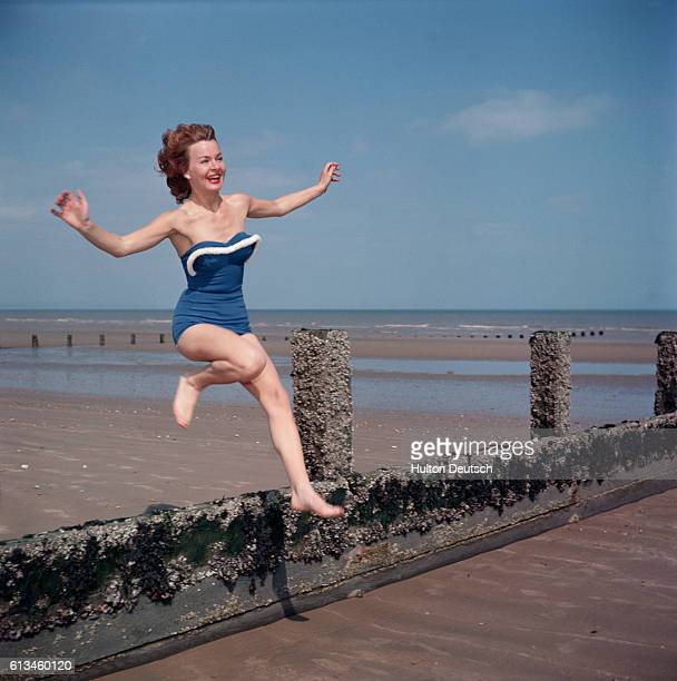 A woman models a blue swimsuit with white cord trimming ca 1950