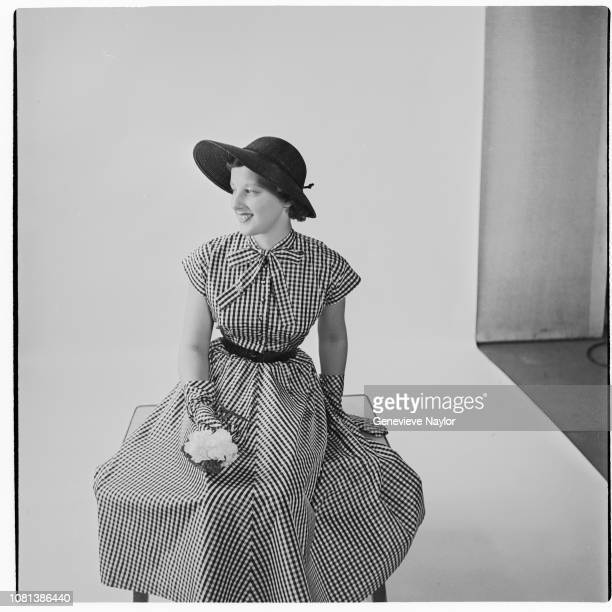 A woman models a checkered BoPeep summer dress and hat for Harper's Bazaar Magazine 1948 | Location Naylor Studio New York New York USA