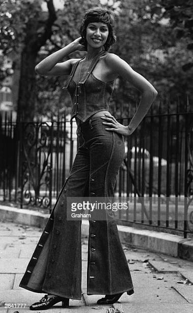 A woman models a denim vest and trouser combination complete with many buttons