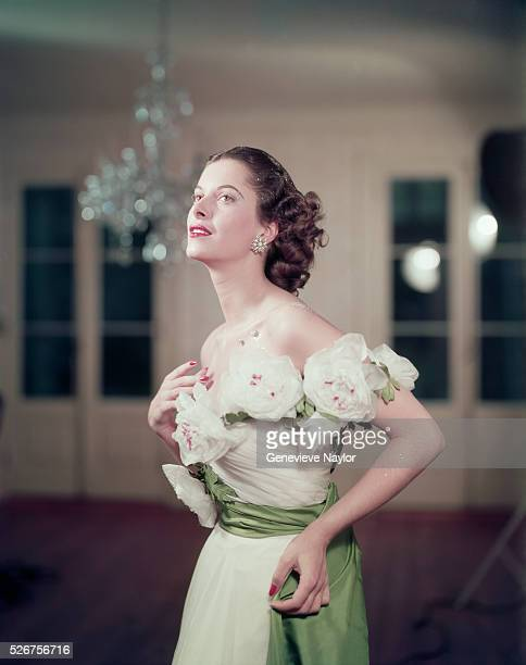 A woman models a gown with large roses around the bodice